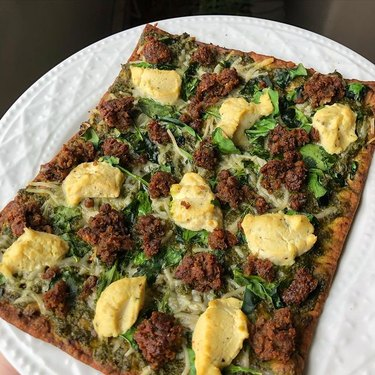 pesto flatbread on white plate using impossible meat