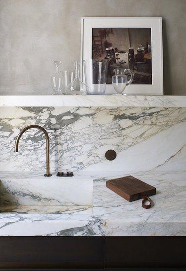 Best kitchen sink materials Marble sink, marble counter, copper faucet, shelf, art, glassware.