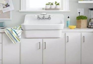 Best kitchen sink materials White cast iron wink, white cabinets, plants, windows.