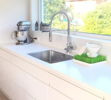 Best kitchen sink materials Stainless steel sink with stainless faucet, white counters, white cabinets, mixer, window.