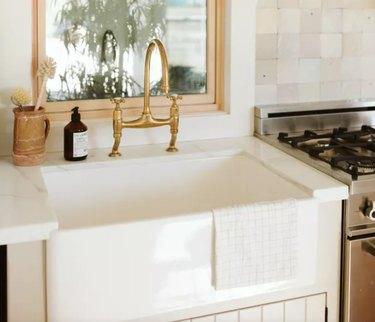 Best kitchen sink materials Farmhouse sink, brass faucet, stove, window.