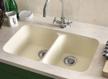 Best kitchen sink materials Cream kitchen sink, stainless faucet, dishes.
