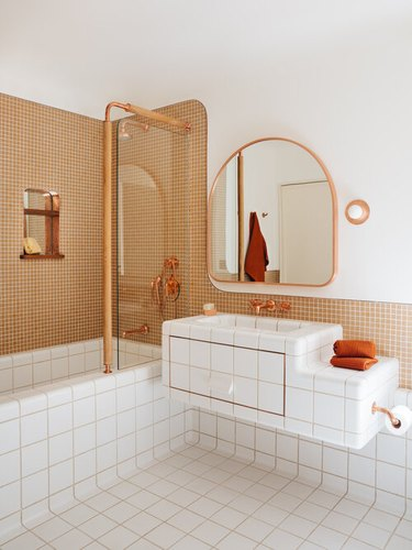 Bathroom designed by Home Studios NYC with copper bathroom faucet and shower