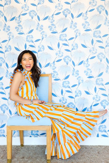 designer roxy te owens on blue wood chair in front of blue floral wallpaper