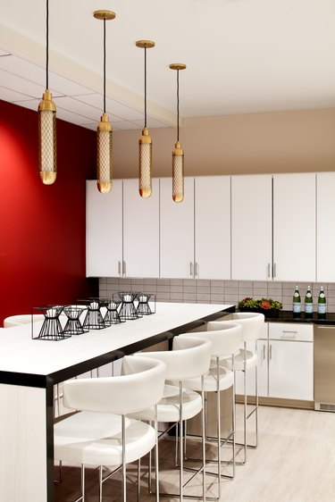 kitchen area with island, white chairs, and hanging light fixtures