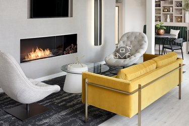 living room space with yellow couch, white chairs and fireplace