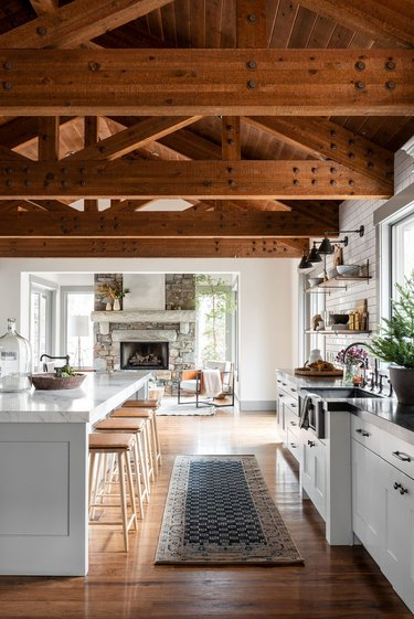 Farmhouse kitchen with exposed beams and vintage runner by Studio McGee