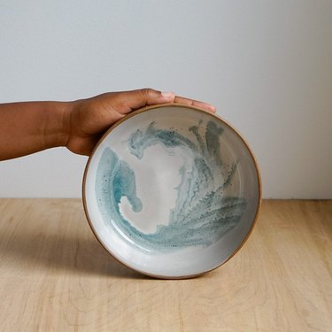 person holding bowl with blue swirl design
