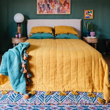 bed with tumeric colored quilt
