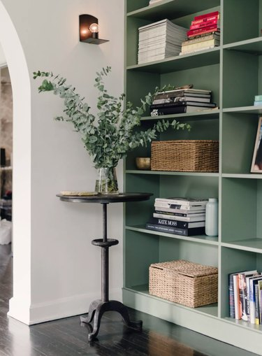 Hallway with round table, plant, bookshelves, sconce.