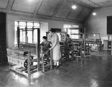 black and white photo of people standing in a weaving studio