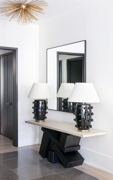 Entryway with pair of black and white table lamps, modern deco credenza, large mirror, gold pendant lamp.