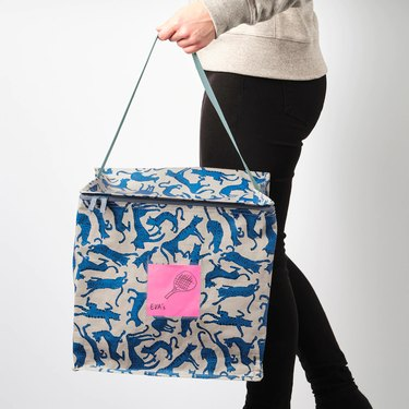 person holding bag in blue cat pattern