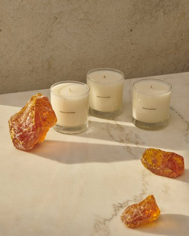 white candles in glass jars with orange crystals
