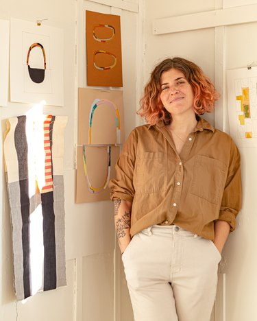 designer sara berks in front of white wall with art