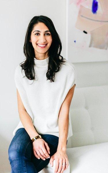 designer nidhi kapur sitting on arm of white couch