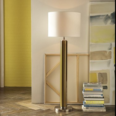 Floor lamp with brass base, white shade in hallway with books, art