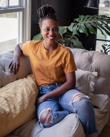 designer Shavonda Gardner on beige couch with yellow pillow