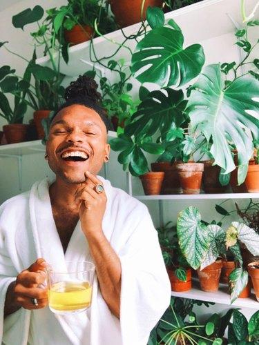 person in white robe near plants