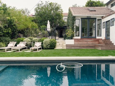 A white house with steps leading down to the backyard; an in-ground pool surrounded by a green lawn