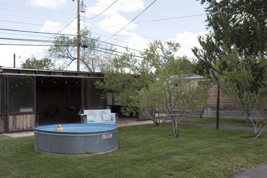 A backyard with a stock tank pool and small trees