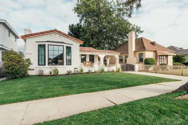 A Spanish-style home with a green front lawn