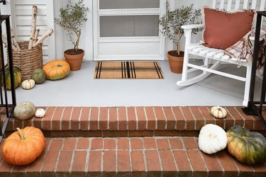 Plaid doormat, firewood basket, potted olive trees and pumpkins on fall porch