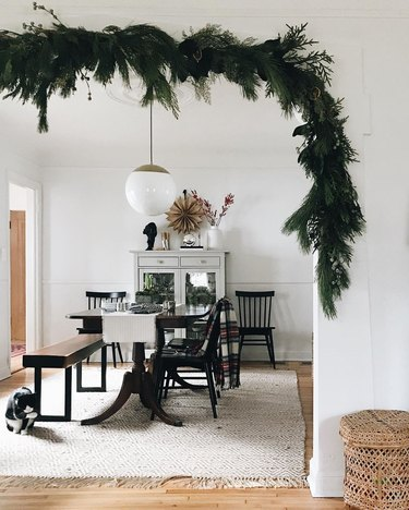 contemporary Christmas decor with garland hung in the doorway to dining room