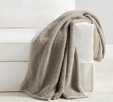 gray fuzzy teddy blanket on white sofa