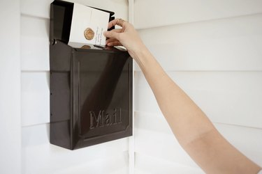 Placing envelope with wax seal into mailbox on porch wall