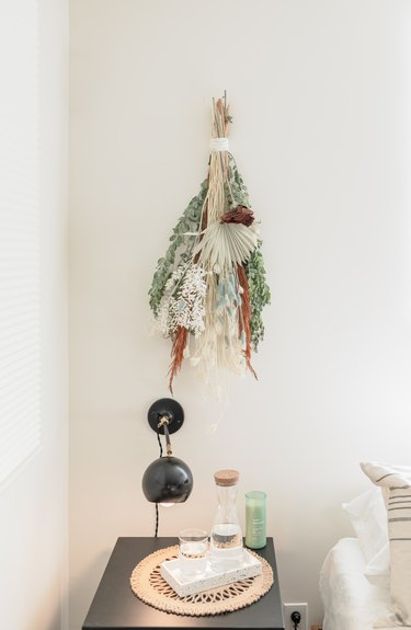 Dried floral arrangement hanging on wall.