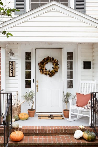 Porch decorated for fall with pumpkins, wreath, logs and rocking chair