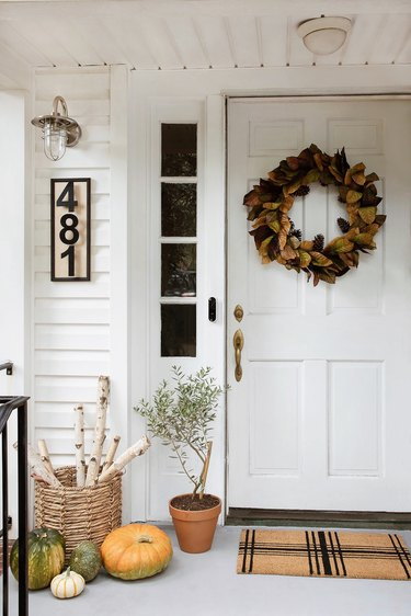 Faux magnolia wreath hung on door with plaid doormat, DIY house numbers plaque, industrial porch light, firewood basket, and pumpkins on fall porch
