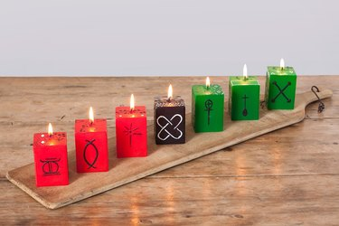 Kwanzaa decorations, red, green, and black kwanzaa cube candles on a wooden board