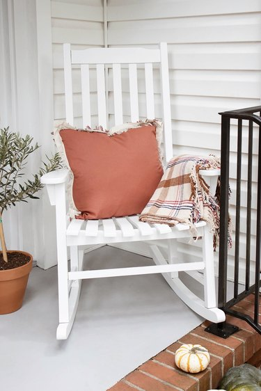 White rocking chair with tan tartan plaid blanket and rust-colored fringe pillow on porch