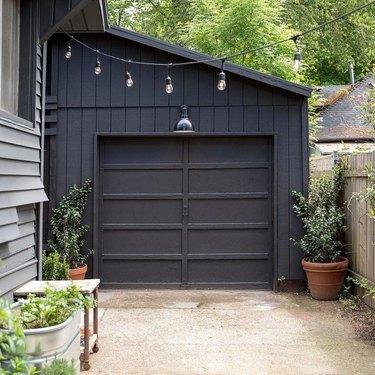 black paneled modern garage doors with modern lighting