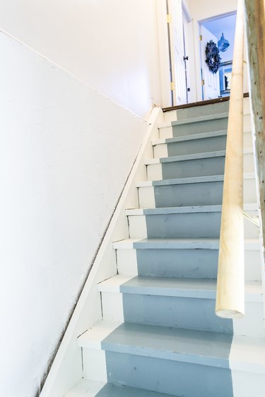 white unfinished basement idea with stairs with painted blue runner