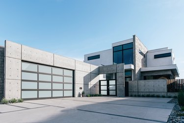 concrete house with glass and metal modern garage doors