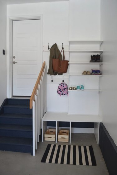 small garage mudroom with rug and shelves