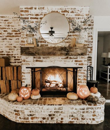 fall fireplace mantel idea with weathered books and an assortment of pumpkins