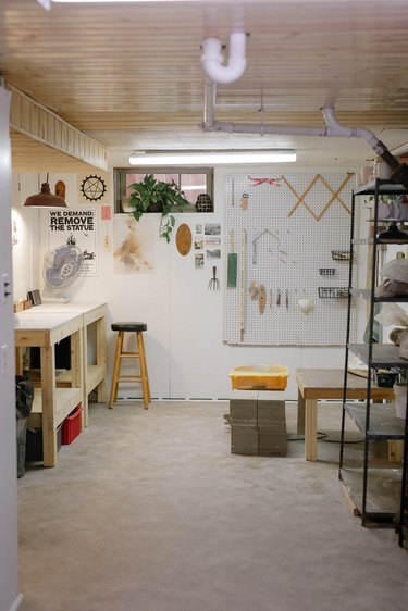 white unfinished basement idea with workspace and shelving