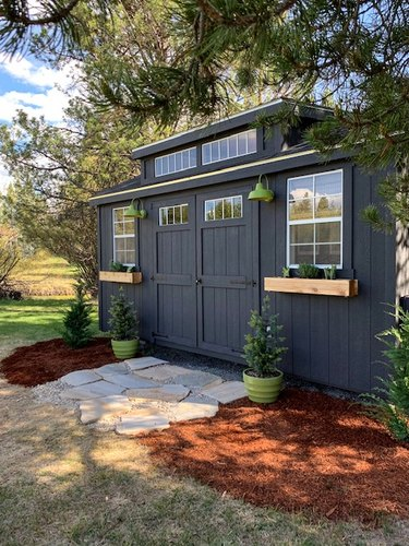 Contemporary shed in black with green barn lights and green planters