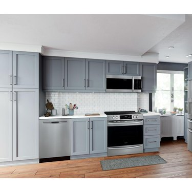 Stainless Steel Gas Stovee with microwave above, light gray cabinets, dishwasher and white subway tile backsplash.