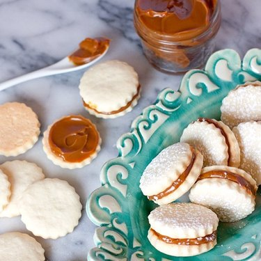 Muy Bueno Cooking Alfajores on blue plate with side of dulce de leche sauce