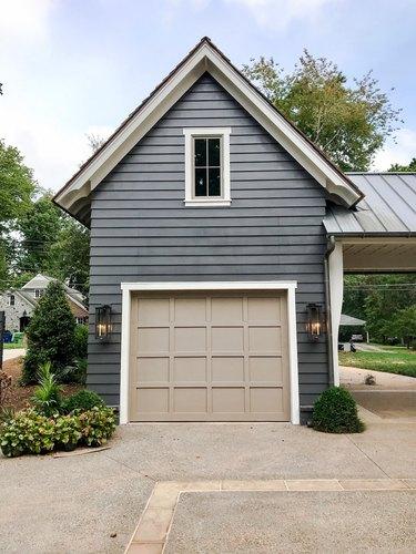 Farmhouse garage door in beige with dark gray exterior and lantern sconces