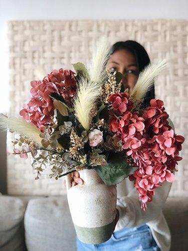 YouTuber Nastazsa holding faux flower arrangement.