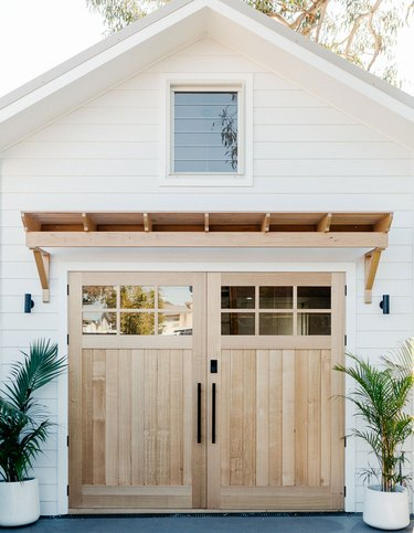 Farmhouse garage doors in wood with wood pergola and white exterior