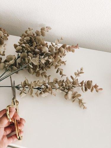 Cutting faux eucalyptus stems.
