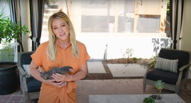 hilary duff on her backyard patio holding a small chicken