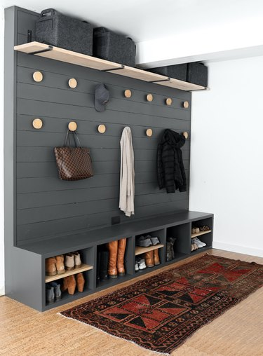 gray garage mudroom with built-in storage and handmade coat hooks